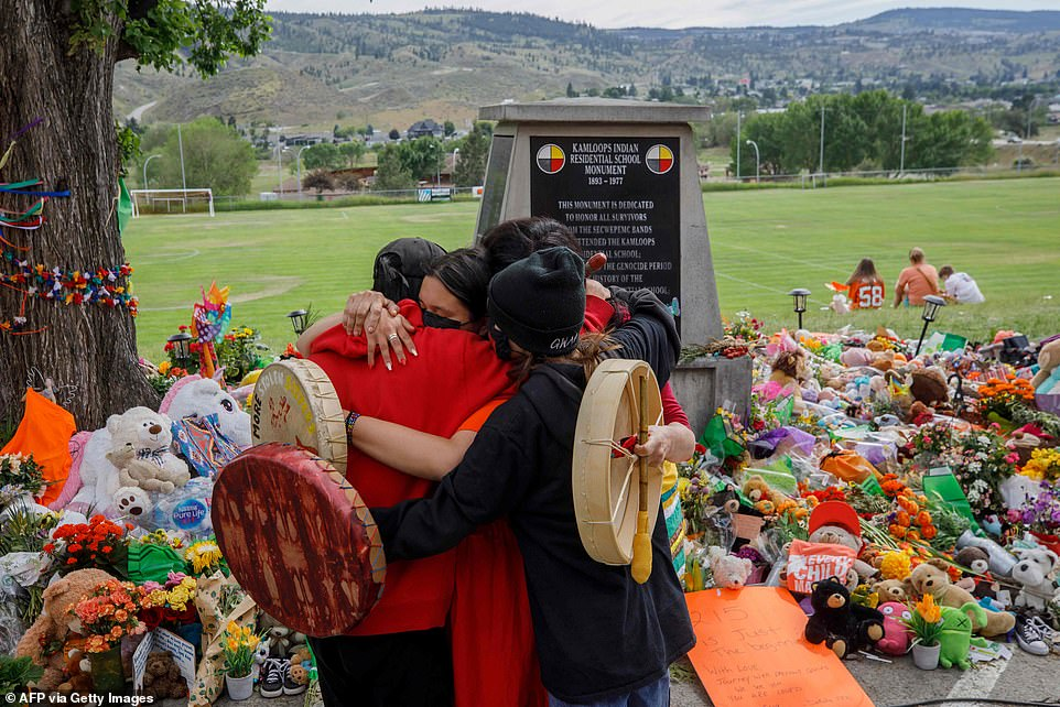 People from Mosakahiken Cree Nation hug in front of a makeshift memorial at the former Kamloops Indian Residential School on June 4 to honor the 215 children whose remains have been discovered buried near the facility, in Kamloops, British Columbia, Canada
