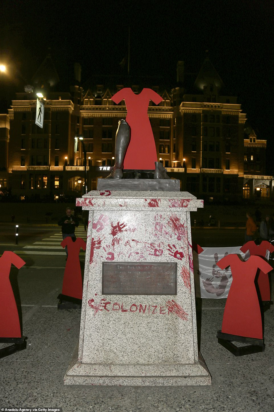 A wooden red dress symbolising the struggle of indigenous people in Canada and severed bronze leg of Capt. James Cook's statue in Victoria, British Columbia, where the monument was pulled down by a crowd and dumped into the harbour.'Colonizer' was daubed on the plinth