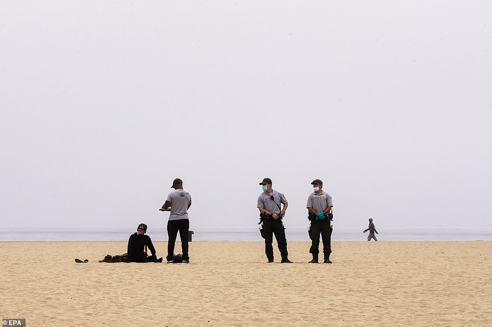 Rangers talk to a man on the beach amid an operation to remove homeless encampments from the beach front in Venice Beach
