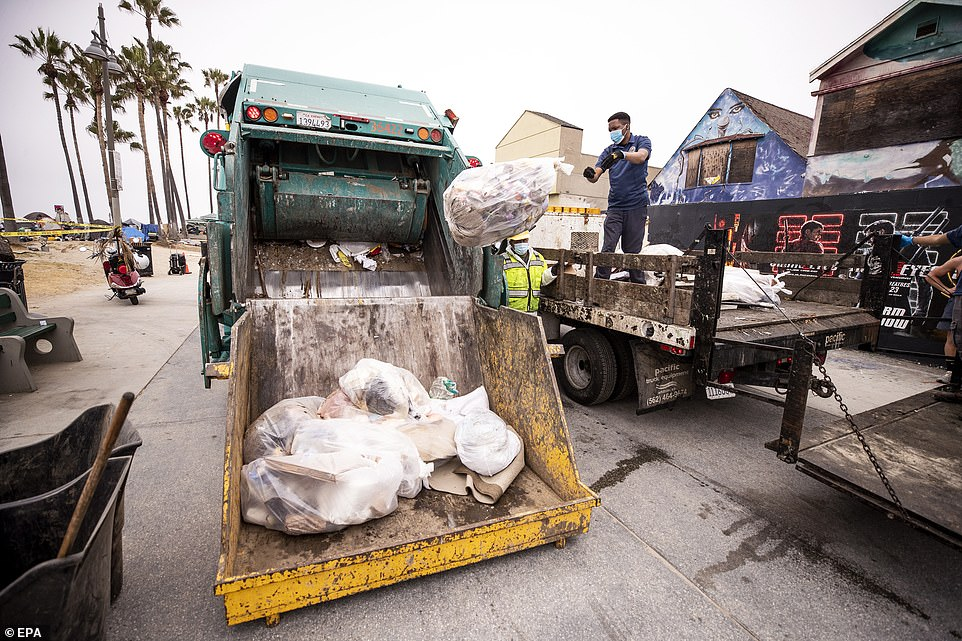 A Los Angeles sanitation services employee throws garbage bags in a truck amid an operation to remove homeless encampments from the beach front in Venice Beach on Friday