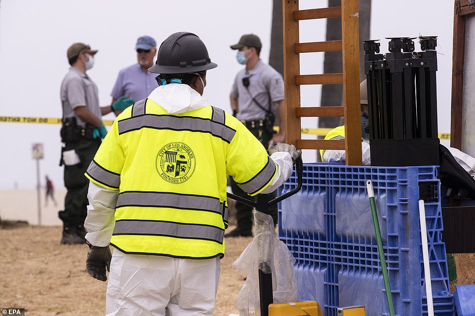Los Angeles sanitation services employees clean up Dixie's encampment amid an operation to remove homeless encampments from the beach front in Venice Beach