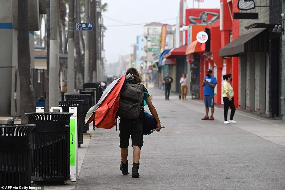 A Los Angeles man carries a tent as authorities begin clearing homeless encampments at the Venice Beach Boardwalk