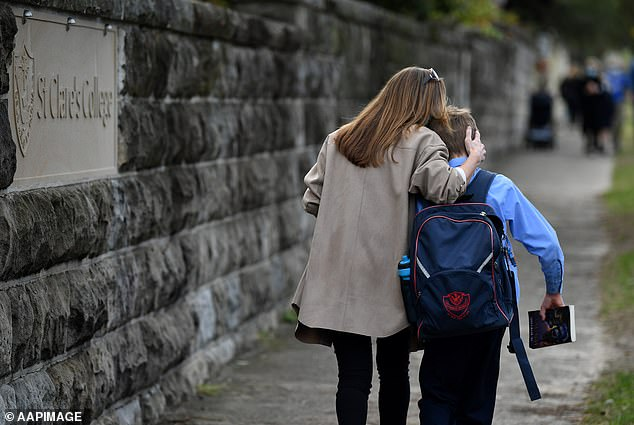 As part of the extended lockdown, schools will be shut with at-home-learning taking the place of face-to-face classes (pictured, parents collect children at St Charle's Primary School at Waverley in Sydney, June 22, after a child became infected with Covid-19)