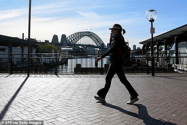 A woman half wears her face mask to speak on her phone as she walks along a quiet Circular Quay in Sydney on Tuesday (pictured) - with masks mandatory indoors until at least July 16