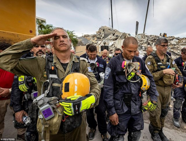 A member of the Israeli search and rescue team dispatched to help with the effort saluted during Wednesday's moment of silence to mark the end of rescue operations at the collapsed Surfside condo