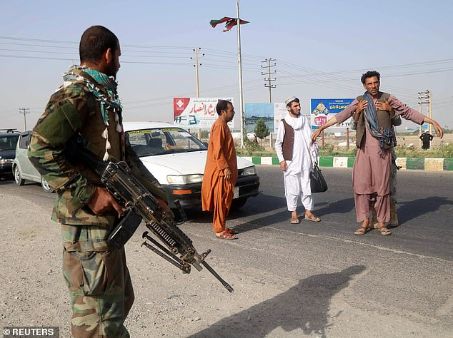 One Afghan, a former solider who is on the Taliban's hit list, said locals feel 'helpless' as the Taliban sweep across the country. Pictured:An Afghan National Army (ANA) soldier searches a man at a checkpoint in the Guzara district today