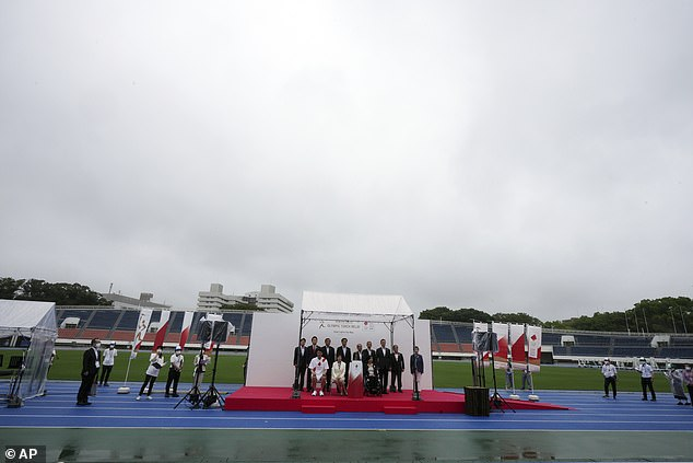 The Olympic flame arrived in Tokyo on Friday to an empty stadium and in pouring rain as the city prepares for a spectator-free games