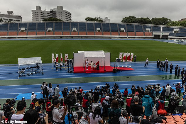 The Olympic flame arrived in Tokyo to an empty stadium and in pouring rain on Friday in front of only a handful of journalists and officials