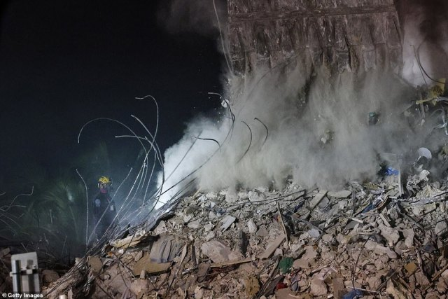 Dust is seen floating through the air as rescue workers remove debris overnight