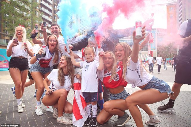 England fans clutch onto smoke canisters and cans of booze as they make their way to Wembley