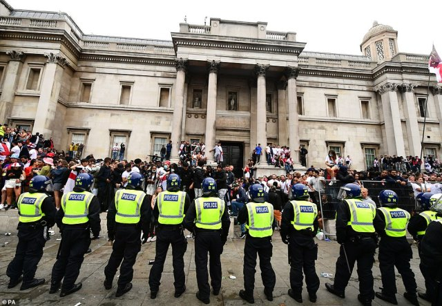 Police monitor fans at Trafalgar Square, London, as chaos begins to ensue ahead of the match between the Three Lions and Italy