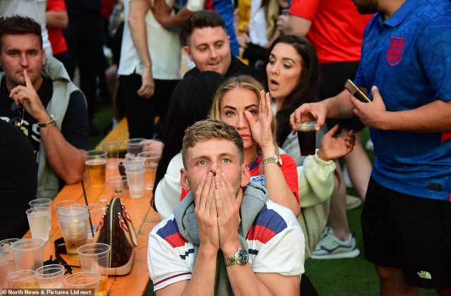 Upset fans hide their faces in their hands as Italy take the lead