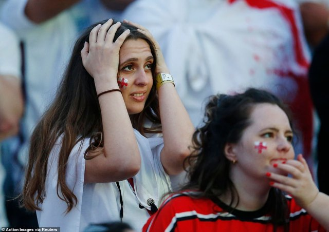A devastated England fan holds her head in her hands