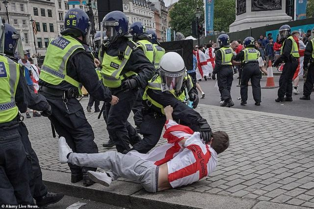 A football fans in held to the ground by police officers as members of the force try to control disorderly behaviour in Westminster