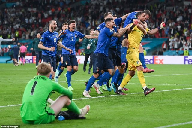 Devastated Jordan Pickford sits on the ground as the Italian side celebrate in front of him afterDonnarumma saved Saka's shot