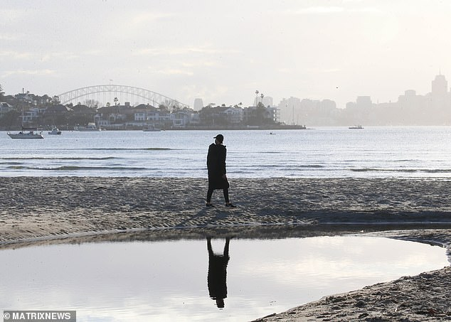 A Sydneysider walks along Rose Bay beach in the city's eastern suburbs. Residents are only allowed to exercise as far as 10km from their homes