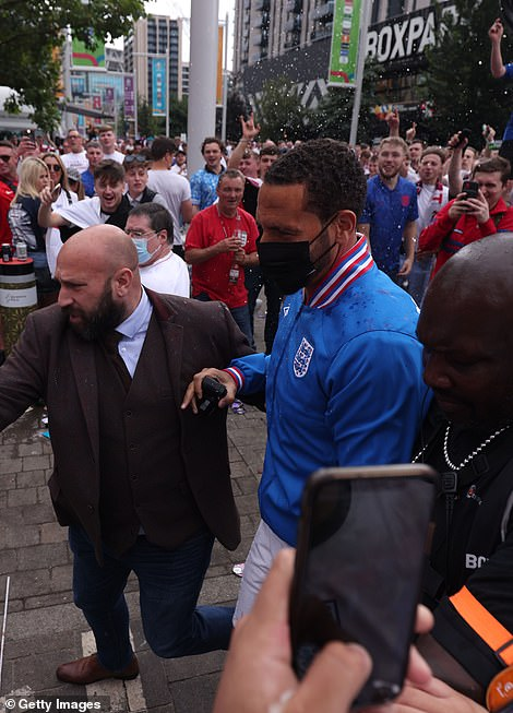 Make way: Rio was flanked by security as he made his way up to the stadium
