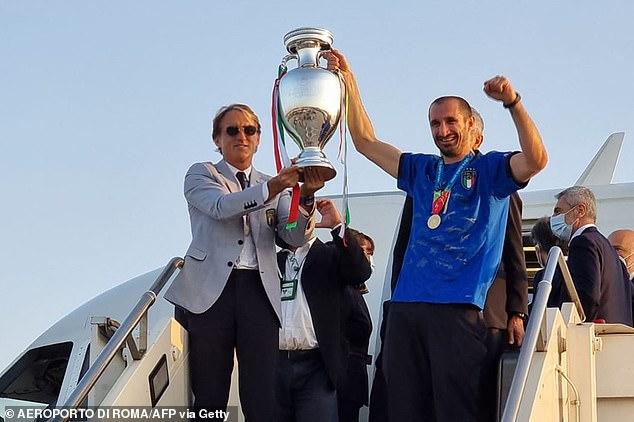 Roberto Mancini lifts the trophy alongsideGiorgio Chiellini as Italy arrive back on Monday