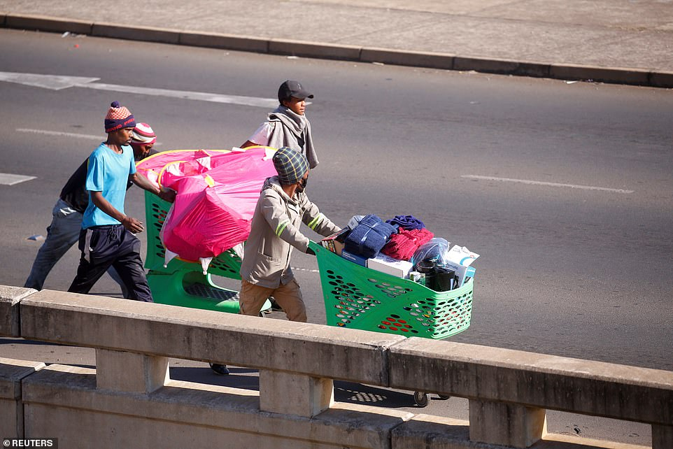 Brazen looters push shopping carts full of stolen goods along the street outside Brookside mall in the city of Pietermaritzburg amid the unrest