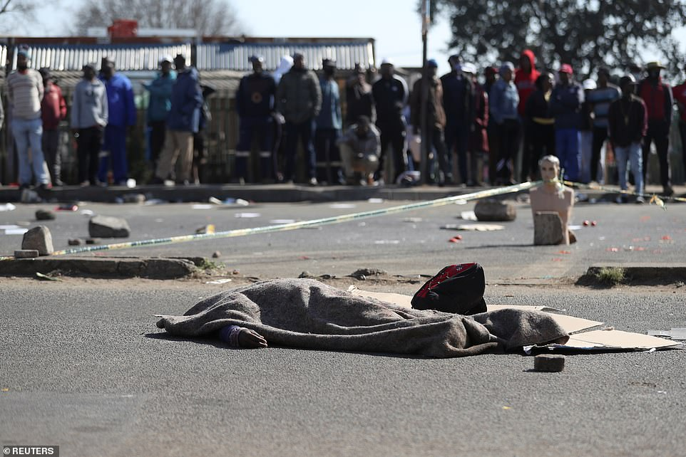 Crowds look at the body of a man as it lies underneath a blanket - one of seven people killed over the weekend amid spiralling violence in the country