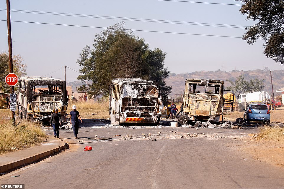 Burned-out buses and trucks are seen on a road close toPietermaritzburg, in KwaZulu-Natal state where the worst of the violence has been located