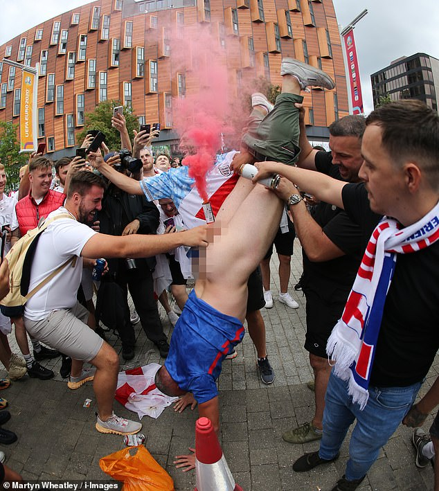 Both the enthusiastic fans - one squatting and one being held in a handstand (pictured in Wembley) - were caught on camera without trousers or underwear with red flares placed in very compromising positions