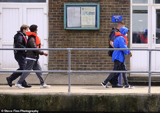 Migrants wear life jacket and rain coats as they arrive to Dover Marina this morning