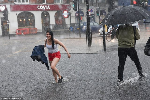 People are left drenched as torrential rain falls down on Turnpike Lane in north London, with the Met Office warning of floods and up to two inches of rain