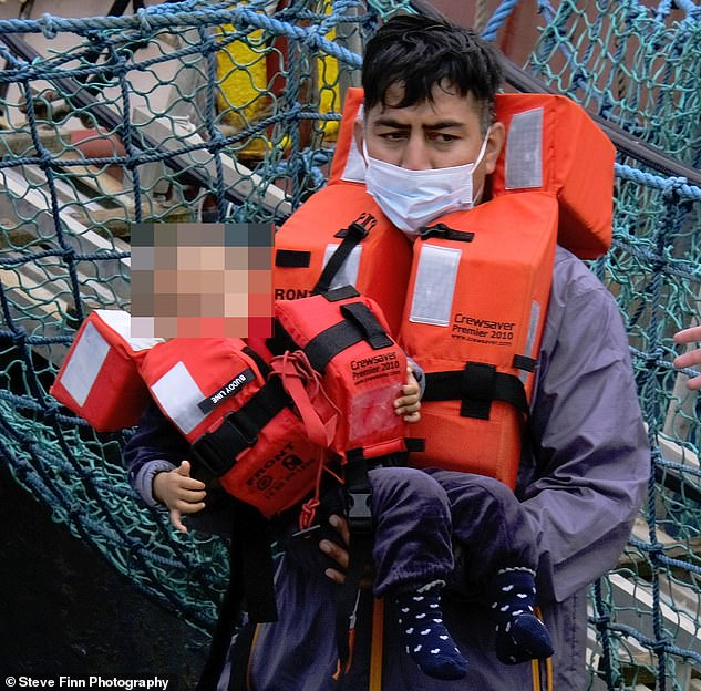 A Border Force officer carries a toddler from a migrant boat in Dover, Kent this morning