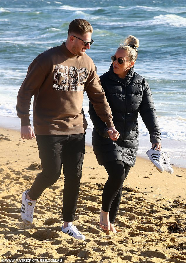 Love is in the air: Married At First Sight's Bryce Ruthven, 32, (left) and fiancée Melissa Rawson, 32, (right) looked positively smitten as they took a romantic beach stroll in Melbourne on Tuesday, a day after announcing they're engaged and expecting twins
