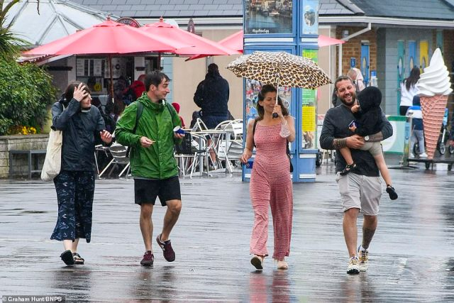 The umbrellas were necessary as the heavy rain set in across parts of the UK. Pictured: Group in Weymouth, Dorset
