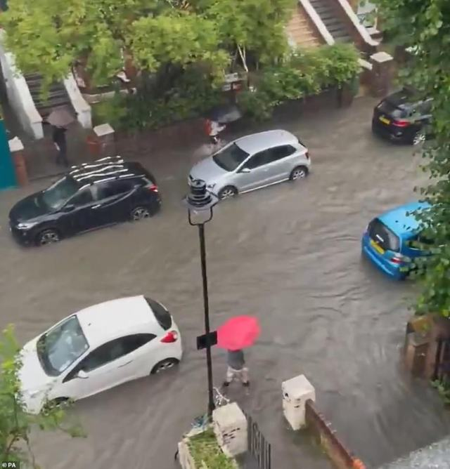 Cars are left abandoned in around 2ft of water after heavy rain falls on a road in South Hampstead, north London, yesterday