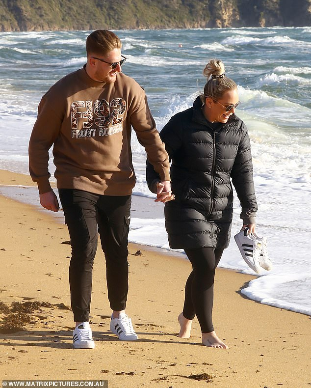 Lovers' lane: The couple, who will become parents for the first time in December, held hands as they made their way down the sand together, before stopping to enjoy an intimate cuddle by the shore