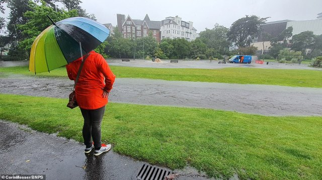 A woman in an umbrella surveys the flooding caused by heavy rain in Bournemouth Gardens on the south coast of the UK