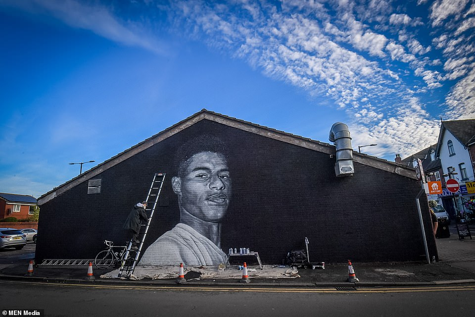 The mural (pictured during creation) on the wall of the Coffee House Cafe in Withington, Manchester, depicts Rashford alongside the phrase: 'Take pride in knowing that your struggle will play the biggest role in your purpose'