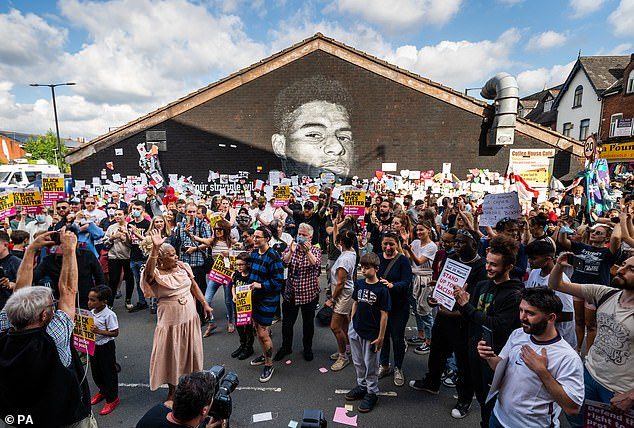 Last night, hundreds of people took the knee beside a repaired mural of Rashford in Withington in a show of support for the striker
