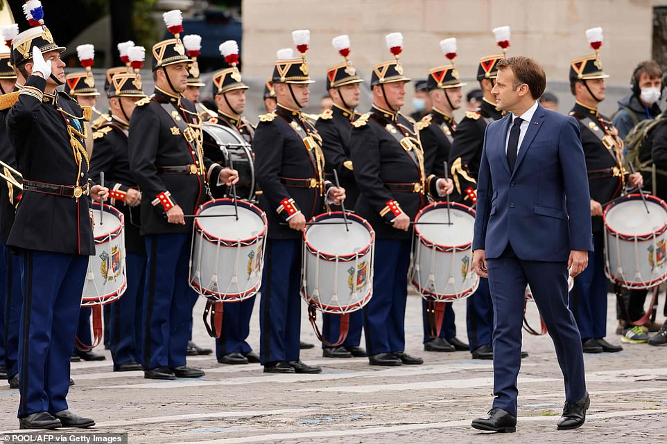 French President Emmanuel Macron reviews troops during the annual Bastille Day military parade