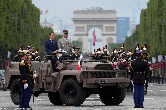 French President Emmanuel Macron (left) and French Armies Chief of Staff General Francois Lecointre (right) stand in the command car during the annual Bastille Day military parade