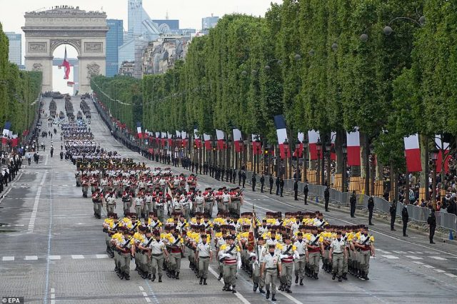 Troops of the Chad regiment parade on the Champs-Elysees avenue during the Bastille Day parade and are followed by thousands of troops