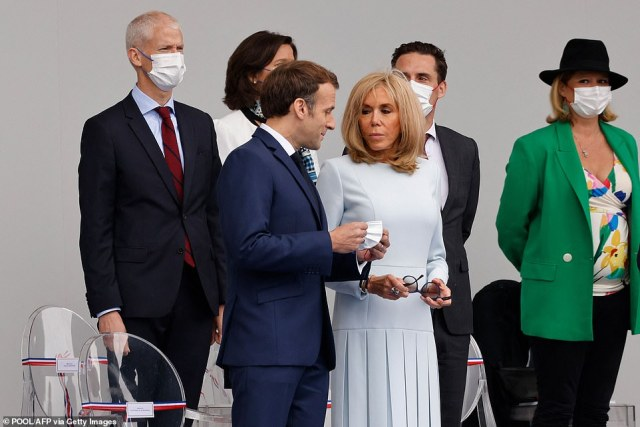 Macron speaks to his wife Brigitte Macron as they attend the military parade on Wednesday