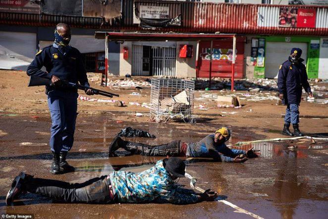 South African police force suspected looters to lie down after apprehending them in Soweto on Tuesday