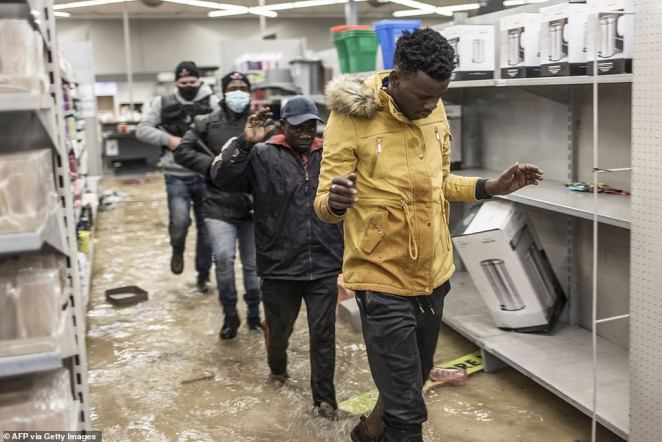 Suspected looters who surrendered to armed private security officers are marched outside in a flooded mall in Vosloorus on Tuesday