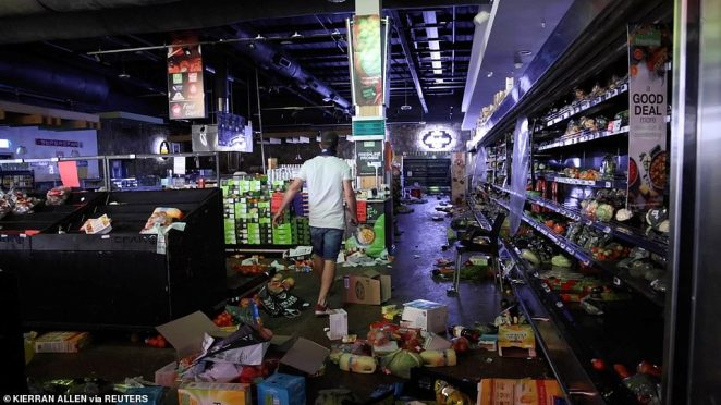 A self-armed local looks for looters inside a supermarket following protests that have widened into looting, in Durban, on Tuesday