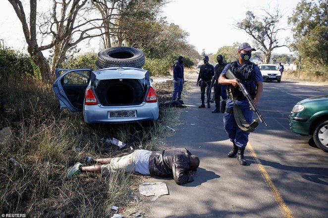 Police officers detain people after violence erupted following the jailing of former South African President Jacob Zuma, in Cato Ridge, on Wednesday