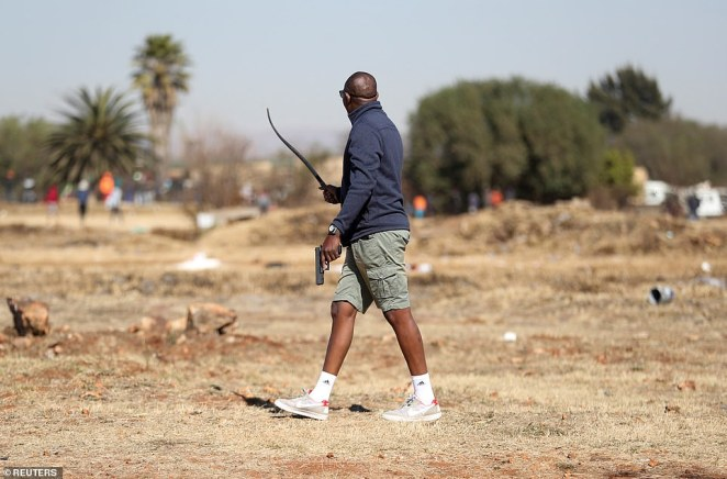 A police officer holds a pistol as the country deploys army to quell unrest in Vosloorus, east of Johannesburg
