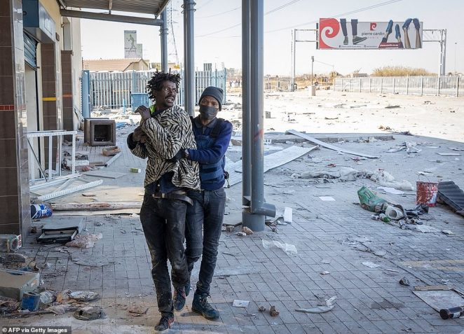 A member of the South African Police Service (SAPS) detains an alleged looter outside the Chris Hanni Mall in Vosloorus, on Wednesday