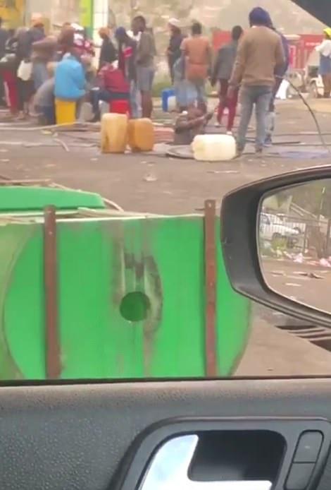 Men siphon gas out of a BP garage outside Durban