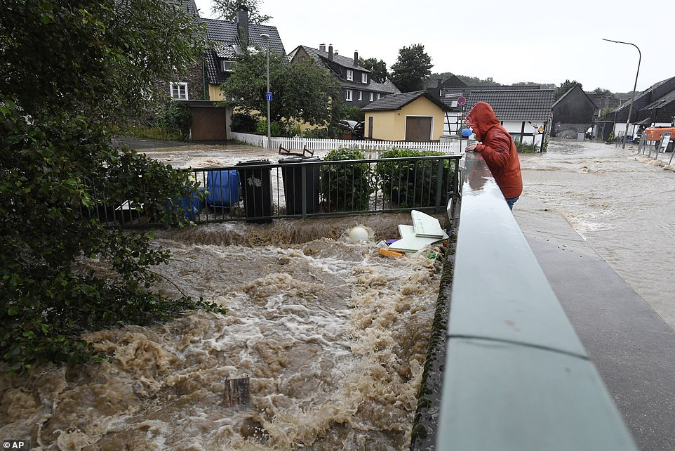 A villager fromBalken, just north of Cologne, looks at floodwaters in theWupper river after torrential downpours overnight caused it to burst its banks