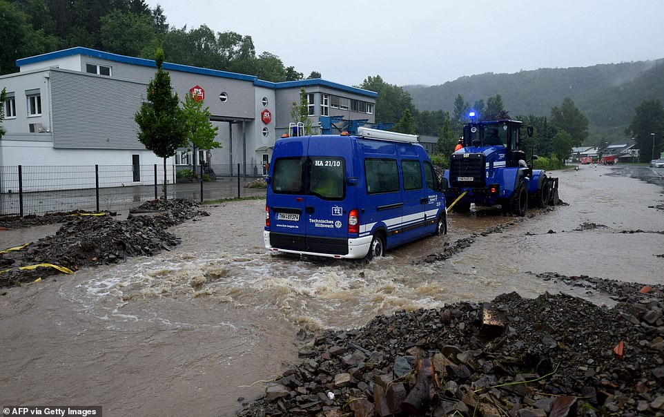 A wheel loader of Germany's technical relief agency THW pulls a stranded van out of floodwaters in Hagen, Germany