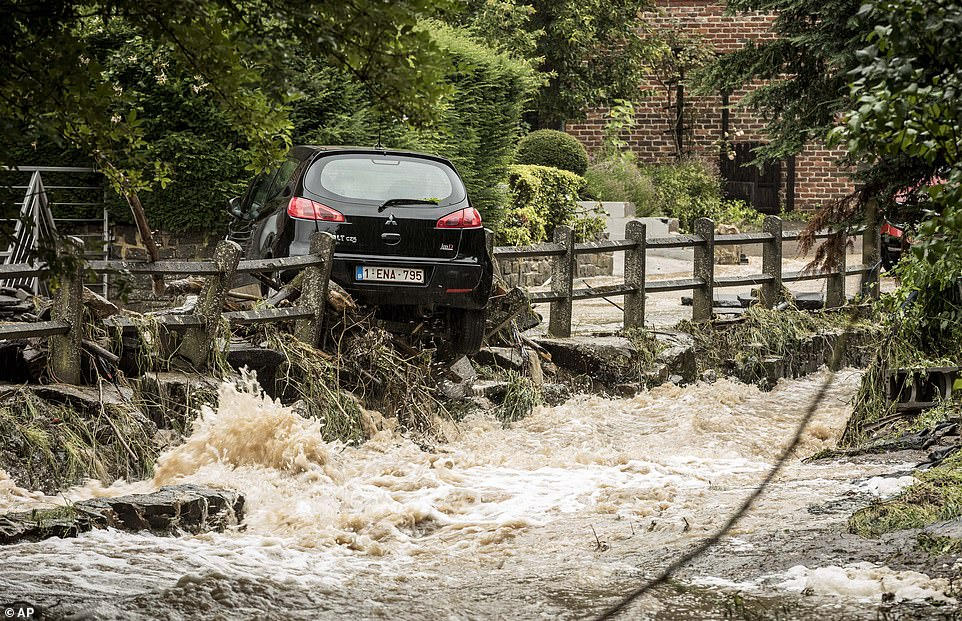 A car sits balanced on a stone wall in a flooded street in Mery, Province of Liege, Belgium